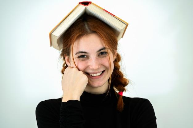 Portrait de drôle jeune étudiante souriante avec un livre ouvert sur la tête. concept de lecture et d'éducation.