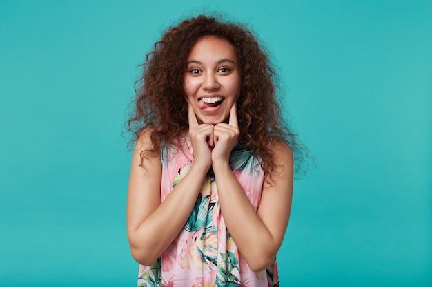 Portrait drôle de jeune femme brune bouclée qui sort sa langue tout en trompant et en gardant les mains levées sur son visage, isolé sur bleu