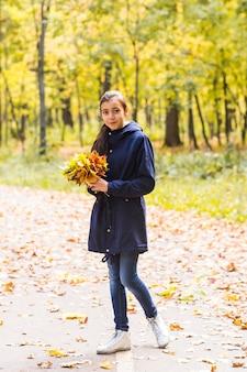 Portrait d'une drôle de jeune fille dans le temps d'automne dans des vêtements chauds et un chapeau