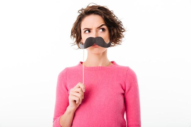 Portrait d'une drôle de jeune fille tenant des moustaches en papier
