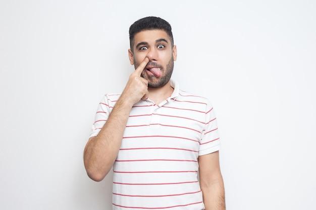 Portrait d'un drôle de jeune homme barbu fou en t-shirt rayé debout, la langue sortie, perçant son nez et regardant la caméra avec une expression stupide. tourné en studio intérieur, isolé sur fond blanc.