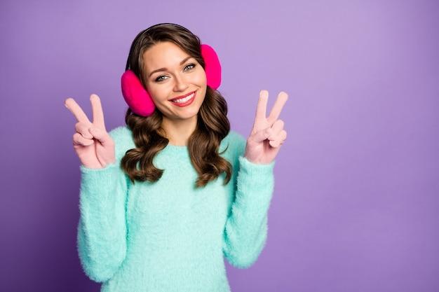 Portrait de drôle jolie dame bonne humeur montrant des symboles v-sign marche rue tenue chaude porter décontracté moelleux pull rose pastel oreille couvre les gants.