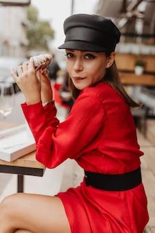 Portrait drôle de jolie fille affamée au café. jeune femme aux cheveux noirs mange un croissant avec brio