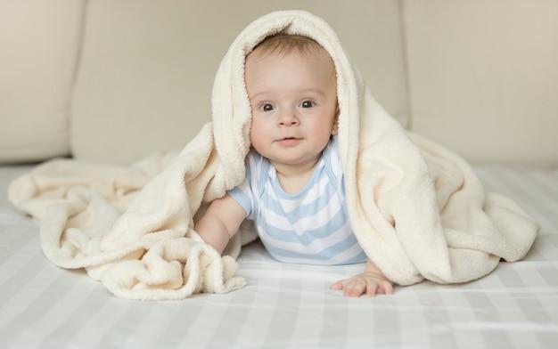 Portrait drôle de petit garçon regardant la caméra sous la couverture