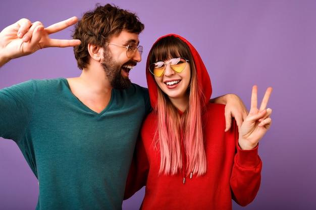 Portrait drôle positif de couple heureux s'amuser ensemble, câlins et rire, famille et amour, vêtements et accessoires de jeunesse décontractés, montrant le geste de paix
