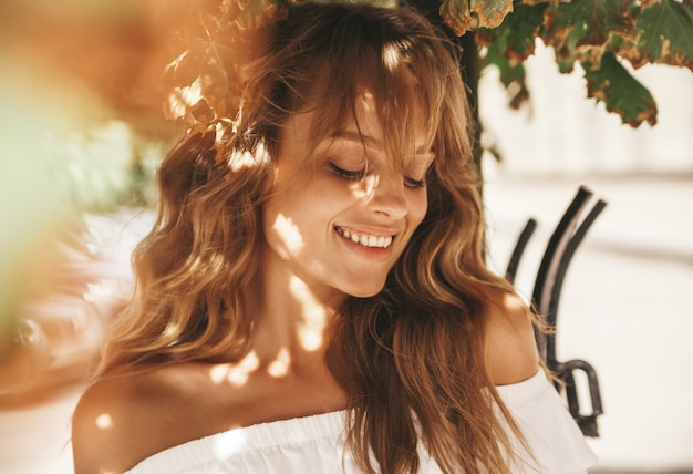 Portrait du beau modèle adolescent blond mignon sans maquillage dans les vêtements de robe blanche hipster d'été posant sur le fond de la rue. lumière du soleil sur le visage
