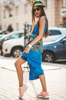 Portrait du beau modèle adolescent brune brune glamour en robe et veste bleu hipster d'été. fille posant dans la rue. femme, lunettes soleil, casquette