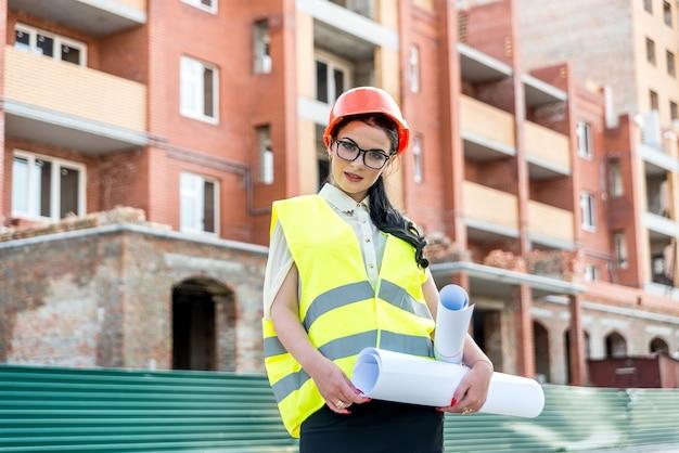 Portrait du bel architecte avec des plans avant la construction