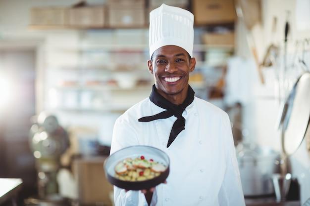 Portrait du chef cuisinier présentant la salade