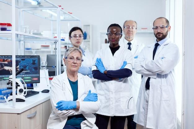Portrait du chef du projet scientifique de son équipe de recherche tenant les bras croisés sur le lieu de travail. scientifique africain de la santé dans un laboratoire de biochimie portant un équipement stérile.