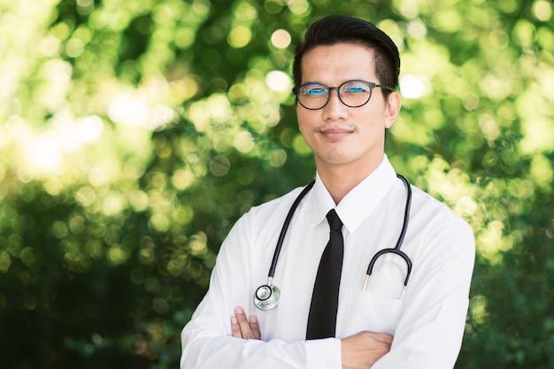 Portrait du docteur asiatique souriant avec des lunettes et stéthoscope au fond de la nature verdoyante.
