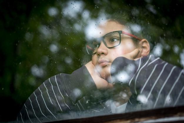 Portrait du garçon regardant par la fenêtre