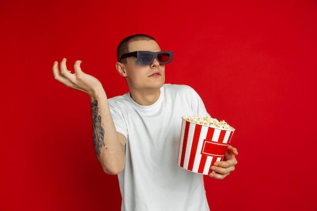Portrait du jeune homme avec des pop-corn sur le mur rouge du studio