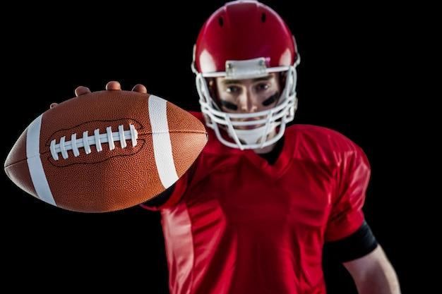 Portrait du joueur de football américain montrant le football à la caméra