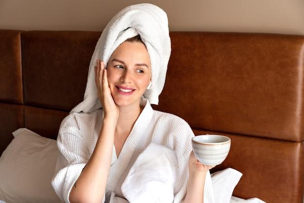 Portrait du matin d'une jolie femme se relaxant au lit après la douche portant un peignoir et une serviette sur la tête, buvant un thé savoureux