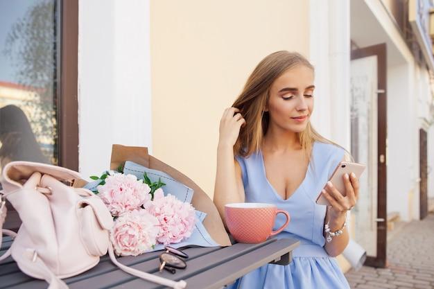 Portrait du message de textos des femmes branchées de la mode moderne par le smartphone