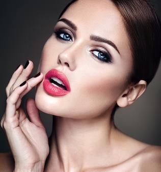 Portrait du modèle de la belle fille avec le maquillage de soirée et la coiffure romantique. toucher ses lèvres rouges