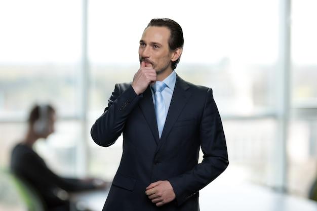 Le portrait du patron réfléchi est debout au bureau. homme d'affaires en costume formel et pensant à quelque chose.