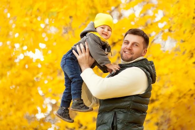 Portrait du père heureux, tenant leur bébé dans le parc en automne