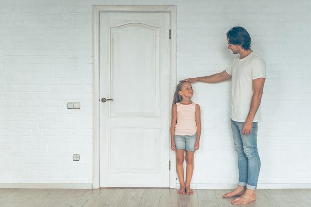 Portrait du père mesurant la hauteur de sa fille mignonne.