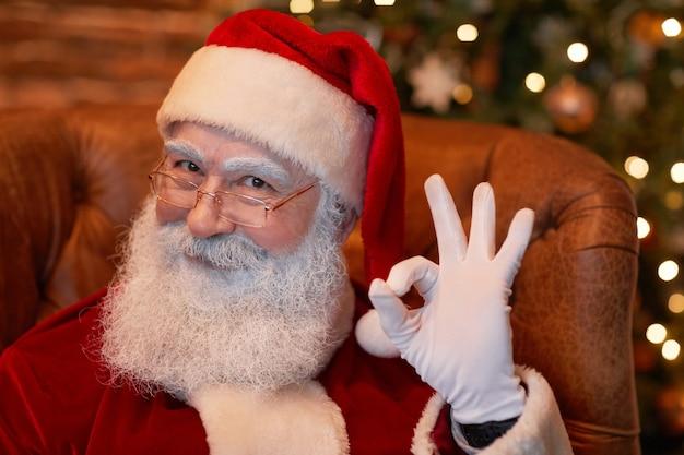 Portrait du père noël à barbe blanche d'âge satisfait à lunettes assis dans un fauteuil et montrant ok...