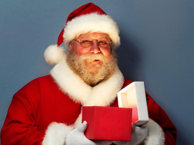 Portrait du père noël tenant une boîte-cadeau ouverte.