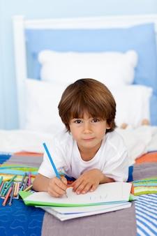 Portrait du petit garçon dessin au lit