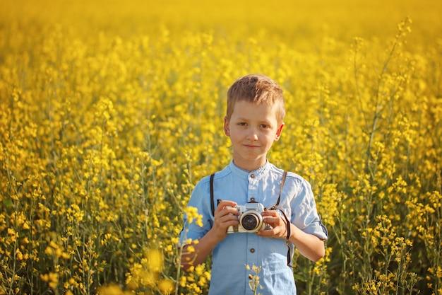 Portrait du photographe de petit garçon avec une caméra sur fond de champ de coucher de soleil jaune