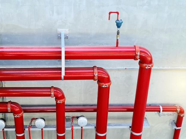 Portrait du système de canalisation d'eau d'incendie rouge contre le mur