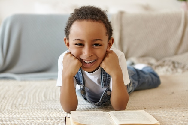 Portrait d'écolier allongé sur le sol et lire un livre dans la bibliothèque à l'école.