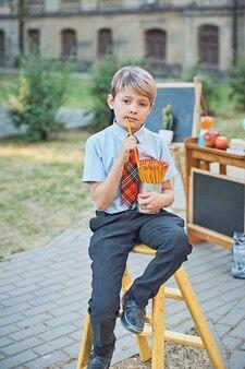 Portrait d'un écolier heureux avec des crayons.