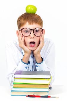 Portrait d'un écolier heureux avec des lunettes tenant une pomme verte sur sa tête