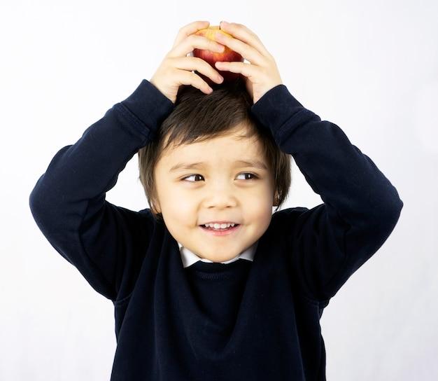 Portrait D'écolier Heureux Mettant Une Pomme Sur La Tête Avec Un Visage Souriant. Photo Premium