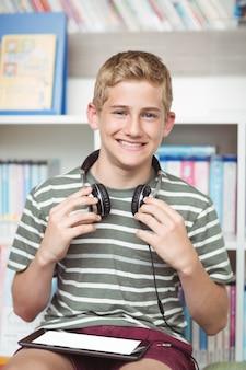 Portrait d'écolier heureux avec tablette numérique et casque assis dans la bibliothèque