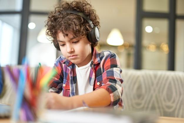 Portrait d'un écolier hispanique concentré portant des écouteurs, préparant ses devoirs assis au bureau à la maison. apprentissage à distance, concept d'enseignement à domicile
