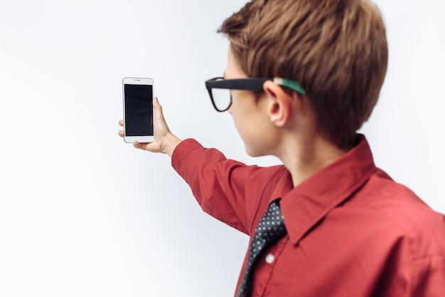 Portrait d'un écolier positif et émotionnel prend un selfie sur votre smartphone