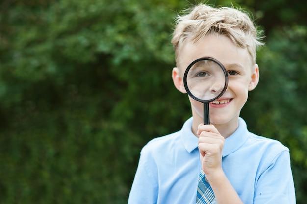 Portrait d'un écolier regardant à travers une loupe
