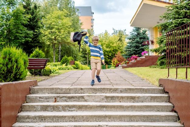 Portrait d'un écolier avec sac à dos sautant