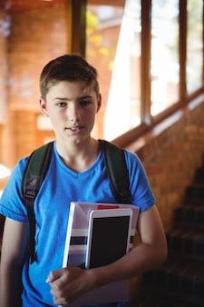 Portrait d'écolier tenant tablette numérique et livre près de l'escalier