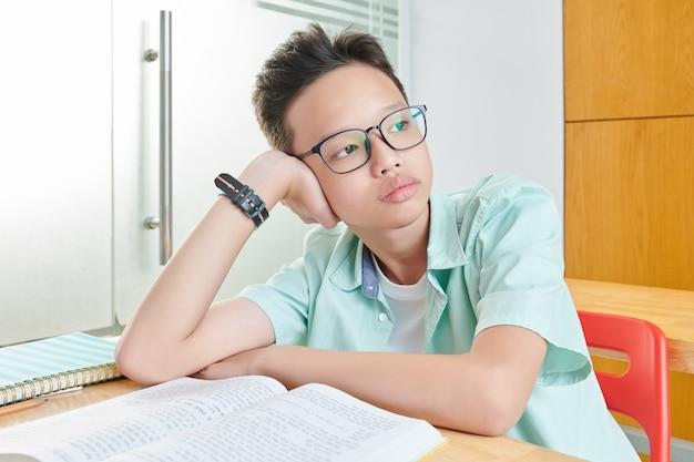 Portrait d'écolier vietnamien s'ennuie pensif dans des verres s'appuyant sur la main et regardant à travers la fenêtre