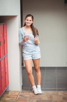 Portrait d'écolière à l'aide de téléphone portable dans le vestiaire