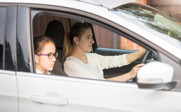 Portrait d'écolière allant avec la mère à l'école en voiture