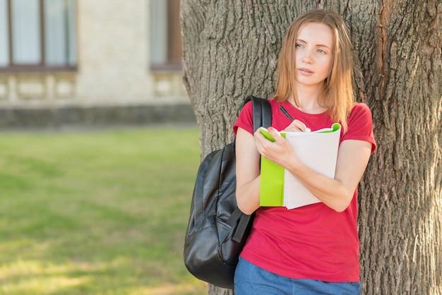 Portrait d'écolière appuyé contre un arbre