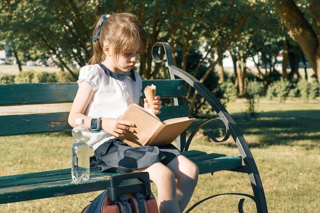 Portrait d'écolière sur un banc de lecture de livre, manger des glaces
