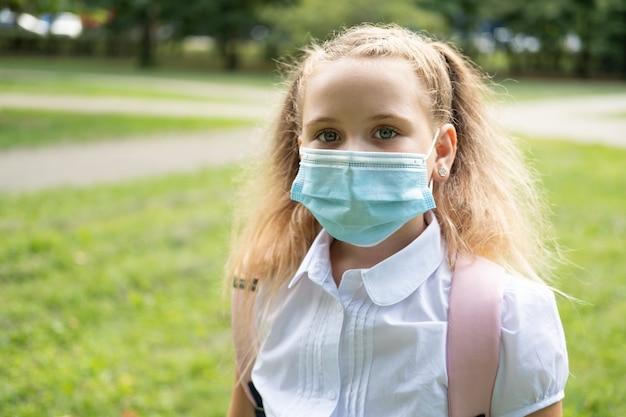 Portrait d'une écolière blonde bouclée en masque de protection en uniforme scolaire avec sac à dos rose à l'école.