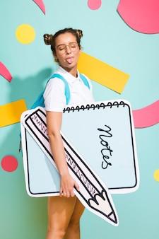 Portrait d'écolière avec gros modèle de bloc-notes