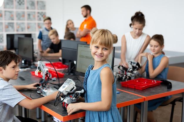 Portrait d'une écolière heureuse dans une classe de robotique, elle tient un robot assemblé à partir de pièces en plastique programmées sur un ordinateur