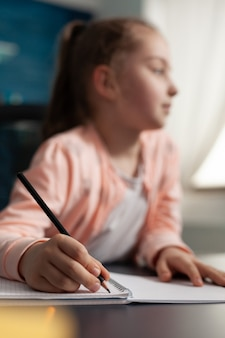 Portrait d'une écolière intelligente écoutant un professeur de réunion de classe en ligne et prenant des notes pour obtenir des informations sur la leçon. enfant apprenant du livre d'étude étant scolarisé à la maison pour la connaissance de l'éducation