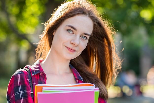 Portrait d'écolière avec des livres dans le parc