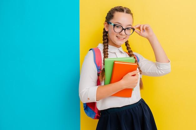Portrait, écolière, lunettes, livres, manuels, jaune bleu